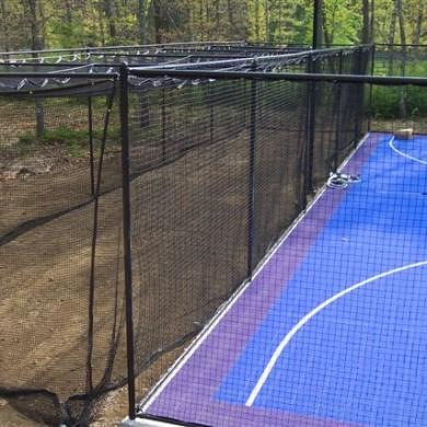 A Sport Court game court with attached batting cage.