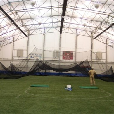 Raising the retractable golf net at the York Sports Center.