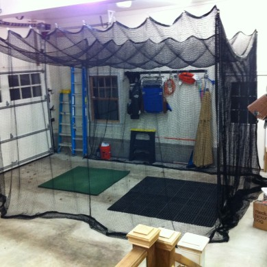Custom, retractable open-golf net in home garage.