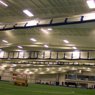 Complete arena construction with ceiling nets, pads, perimeter nets, and three-lift fold curtains at New Hampshire Sportplex.