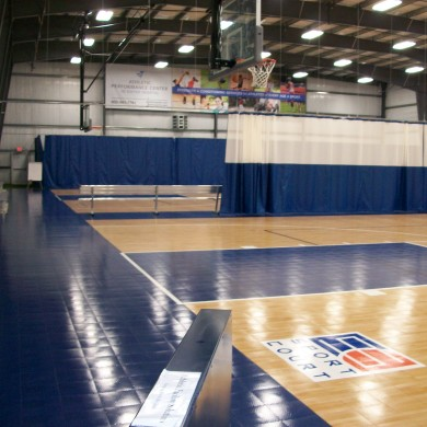 Vinyl curtains (in back) and vinyl mesh curtains on track with Sport Court basketball surface at Above the Rim in Hampton, NH.