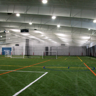 Large, indoor multi-sport arena featuring custom ceiling and perimeter nets, divider curtains and nets, and i beam pads.