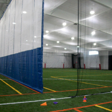 Multi-sport area featuring custom divider curtain and net, ceiling net, and i beam pads.